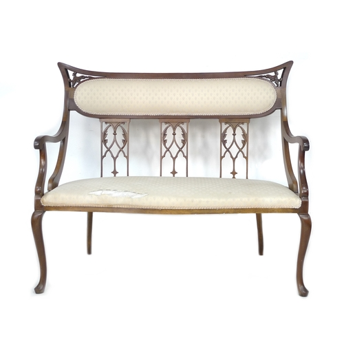 236 - An Edwardian mahogany two seater salon settee, with carved and pierced decoration, cream foliate pat...