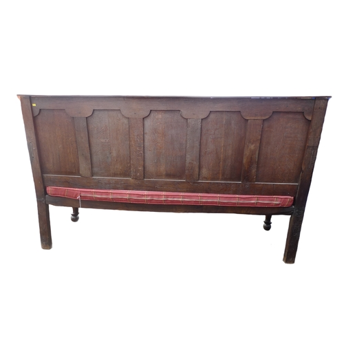 297 - A Georgian oak settle, the five panelled back with fielded outlines, set beneath a moulded rail with...