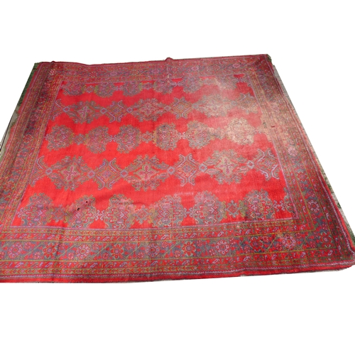 235 - A Turkey carpet with red ground, five rows of conjoined medallions in blues and greens, multiple bor...