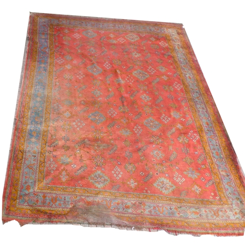 229 - A Persian Ushak carpet with red ground, field decorated with blue and orange flower motifs, multiple...