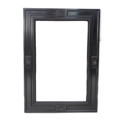 266 - An early 20th century ebonised wall mirror, with bevelled rectangular plate, carved parallel frame s...