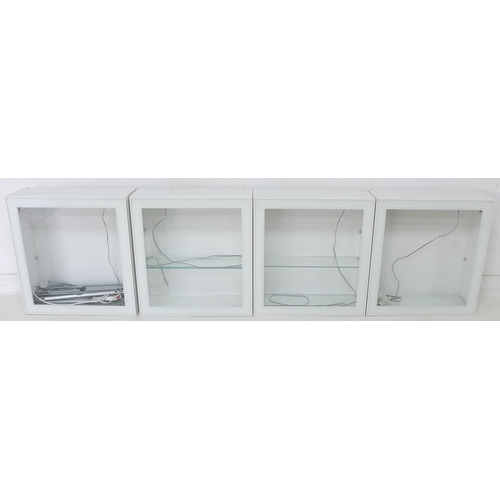 219 - A group of four Ikea white wall mounted cupboards, each (23 x 60 x 64cm high) with single glazed doo...