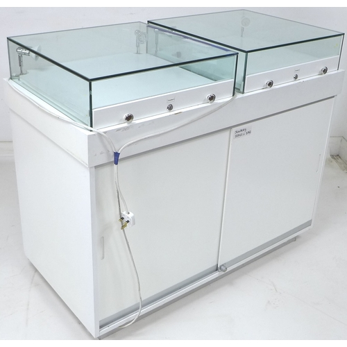 224 - A modern white MDF shop display counter, with two top mounted glazed display cases fitted with light...