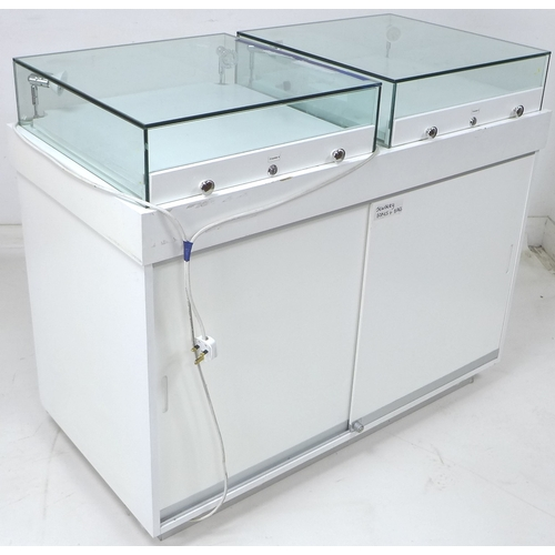 220 - A modern white MDF shop display counter, with two top mounted glazed display cases fitted with light...