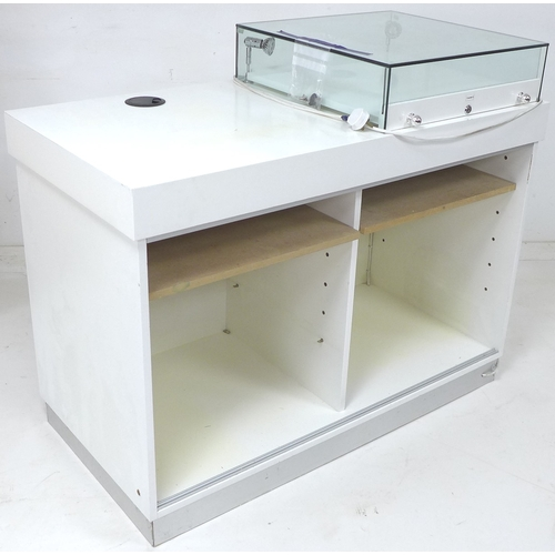 226 - A modern white MDF shop display counter, with single top mounted glazed display case fitted with lig...