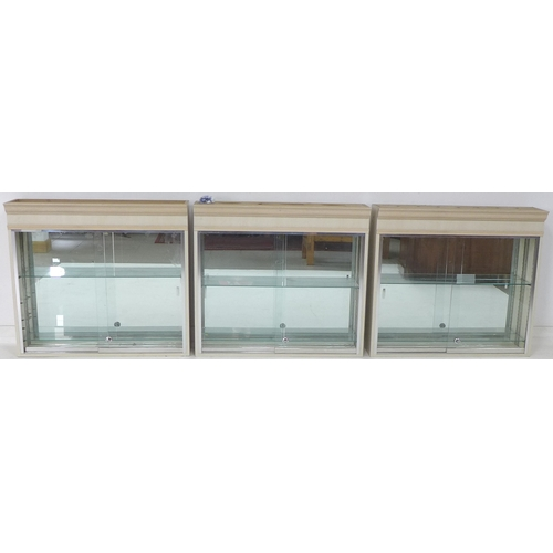 225 - A group of three wall mounted display cabinets, with mirror backs, single glazed doors, and glass sh...
