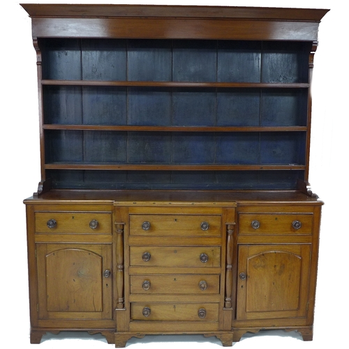 276A - An early 19th century mahogany Welsh dresser, wide cornice over a three shelf plate rack with the ba...
