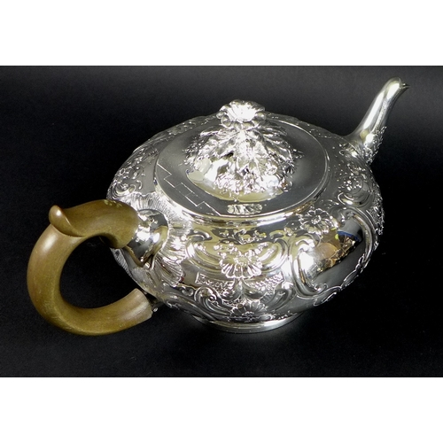 36 - A George III silver teapot, decorated in Rococo style with repousse foliate and floral scrolls, Rich...