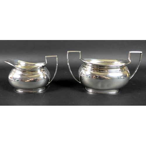 38 - A George V silver three piece tea service, London shape, comprising teapot, twin handled sugar bowl,...