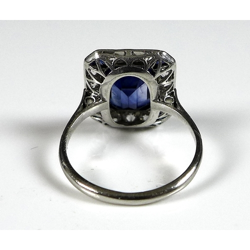 222 - An Art Deco style synthetic sapphire and diamond dress ring, circa 1980, with central emerald cut st...