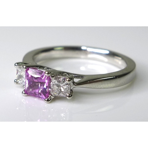 277 - A platinum, pink sapphire and diamond ring, the central emerald cut sapphire of approximately 0.6ct ...