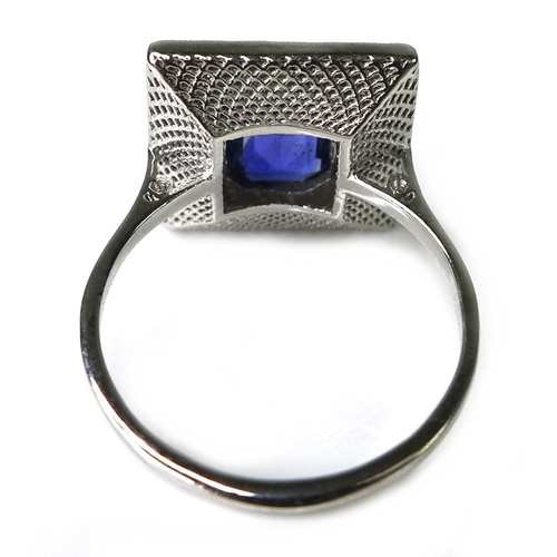 306 - An 18ct white gold, sapphire and diamond Art Deco style ring, the emerald cut central sapphire of ap...