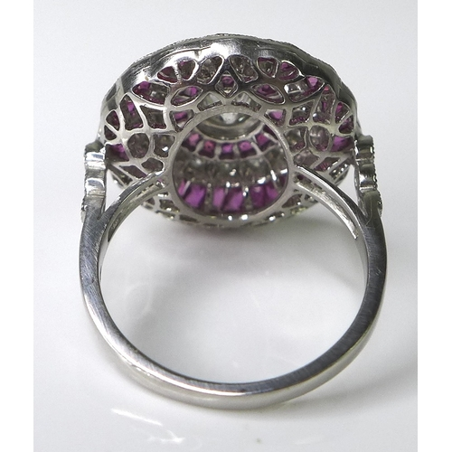 309 - A ruby and diamond dress ring of target design, formed of bands of brilliant cut diamonds and prince...