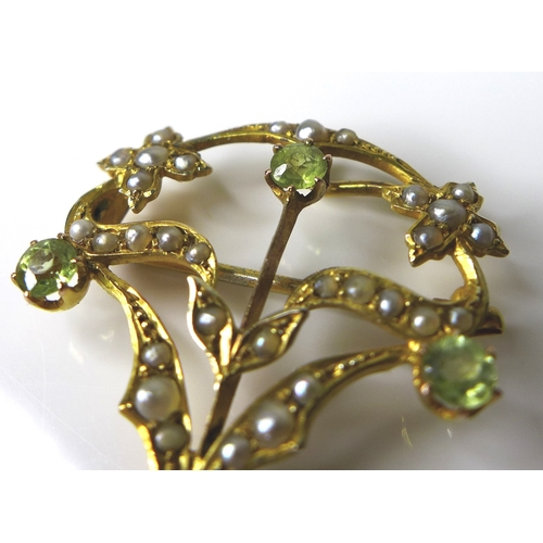 220 - An Edwardian Art Nouveau suffragette brooch set with seed pearls, peridot and amethyst, 4 by 2.8cm....