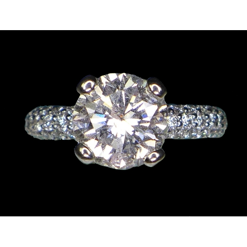 310 - A large and impressive platinum and diamond solitaire ring, the brilliant cut diamond approximately ...