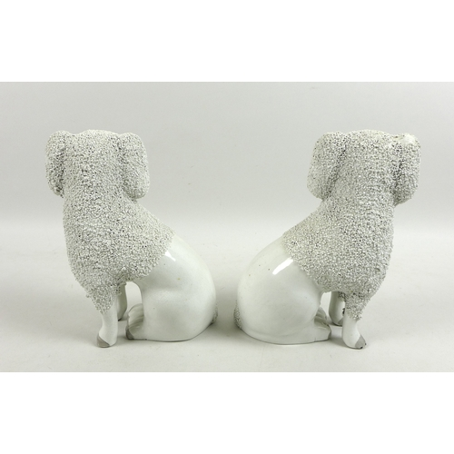 2 - A mirrored pair of Victorian Staffordshire figurines, modelled as seated poodles, with partly encrus...