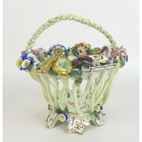 23 - A 19th century porcelain polychrome basket, possibly Coalport, with woven handle, the sides formed a...