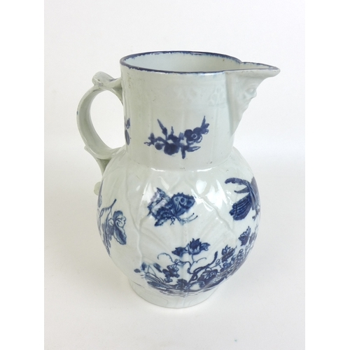 25 - A group of five face mask jugs, comprising three blue and white decorated with sprays of flowers, Sa...