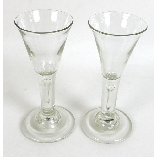11 - A pair of Georgian wine glasses, with trumpet shaped bowls, think stems with single bubble, wide foo...