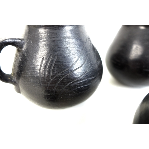 65 - Five pieces of Chinese Longshan style black pottery, comprising two twin handled tea bowls, two sing...