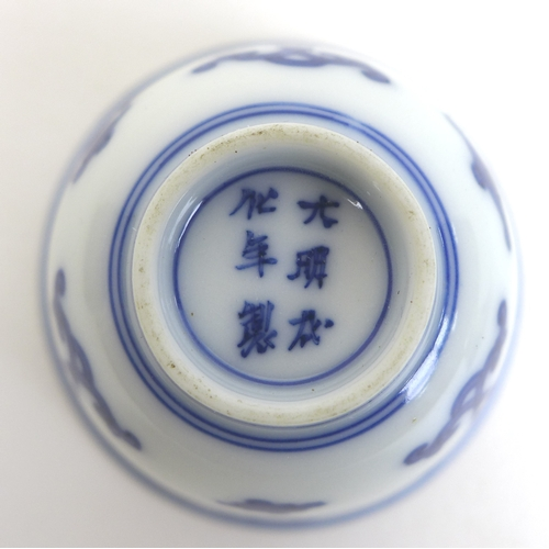 82 - A pair of Chinese Kangxi style blue and white porcelain tea bowls, each decorated with Buddhist symb...