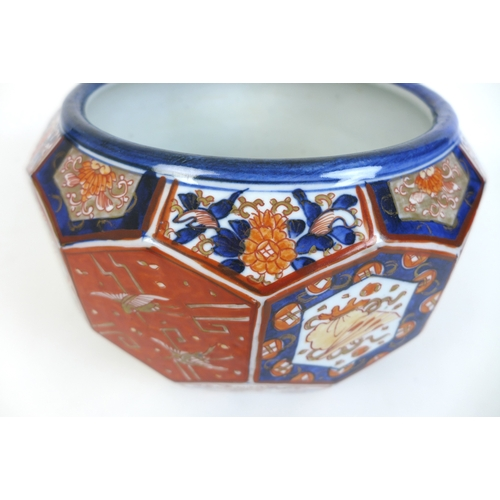 69 - A Japanese porcelain Imari pattern jardiniere, of a multi-faceted hexagonal form, decorated with cra...