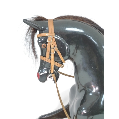 301 - A Haddon Rockers rocking horse, circa 1980s, fibreglass body painted black with brown seat, on a pin...