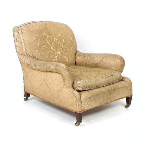 386 - An Edwardian mahogany easy armchair, probably Howard & Sons, Grafton model, with shaped back and ser...