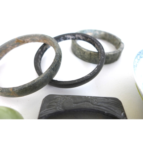87 - A group of eight Chinese jade items and other oriental collectables, three jade hoops, a carved jade...