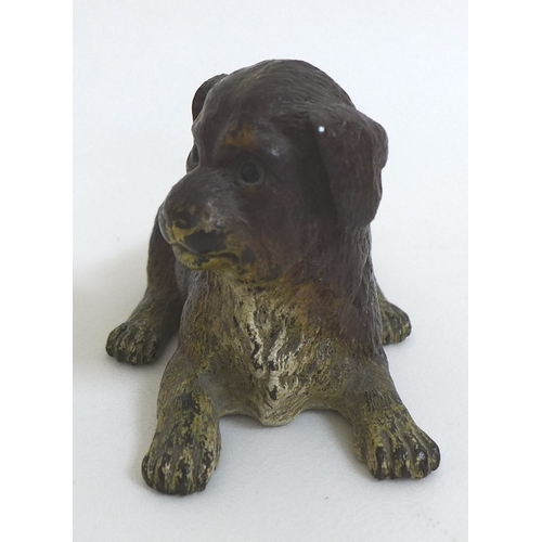 128 - A 19th century cold-painted bronze sculpture, modelled as a recumbent dog, cast stamp 'Déposé' to ba...