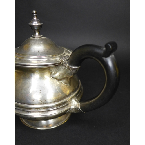 39 - A George V Irish silver tea pot, of compressed baluster form, with plain banding, the hinged cover w...