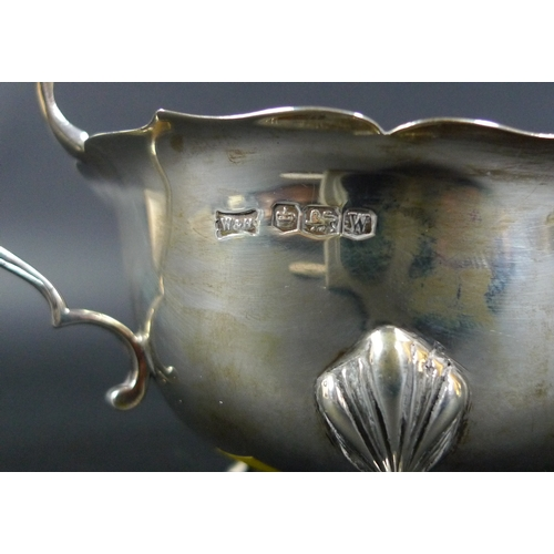 18 - A pair of George VI silver sauce boats, each raised on three hoof feet and with C scroll handles, Wa...
