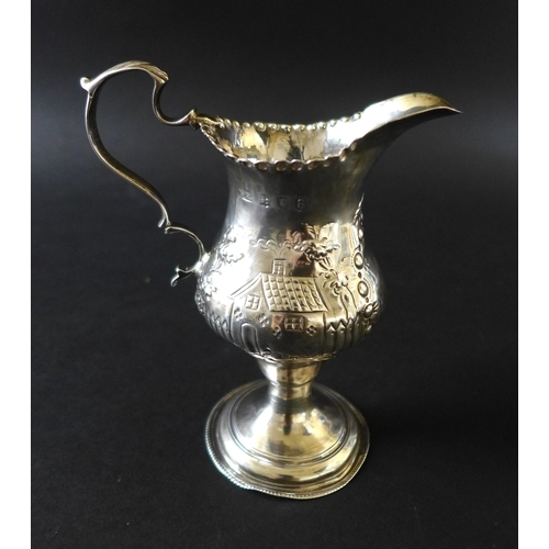 19 - A George III silver cream jug, decorated in Rococo style with a repousse cottage and farm scene desi...