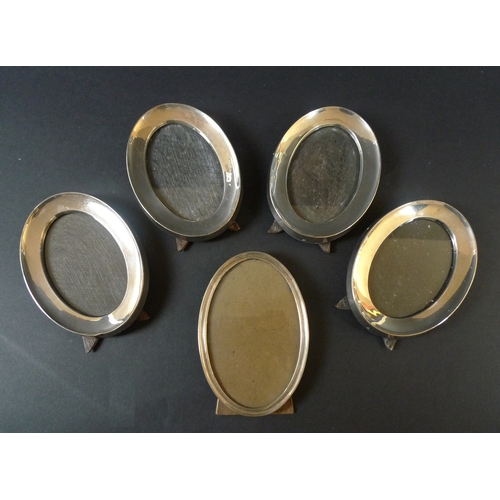 46 - A group of five silver oval photograph frames, comprising a set of four frames, each 14cm oval, Char...