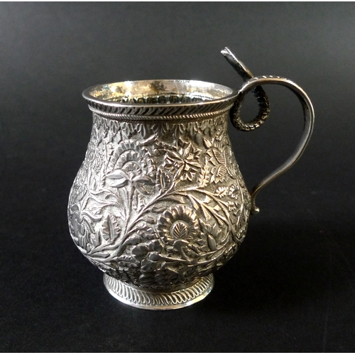 45 - An Indian white metal cup, of baluster form, intricately decorated with flowers and foliage, with a ...