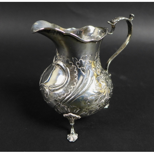 50 - A group of five silver items, comprising a Victorian milk jug with repousse decoration and C shaped ...