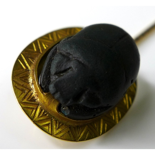 176 - A yellow metal stick pin inset with a ceramic scarab beetle, tests as 22ct gold, 8cm long, 3.8g, wit...