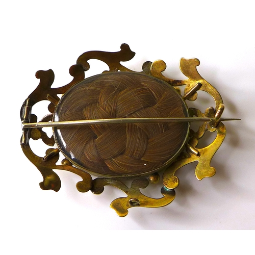 153 - A Victorian yellow metal mourning brooch, with scrolling frame around a glazed oval window set with ...