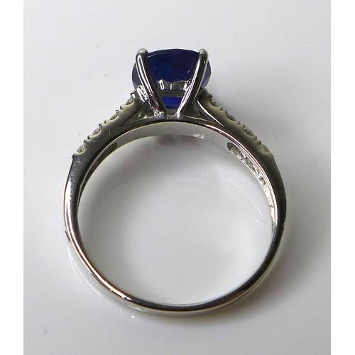 331 - A 14ct white gold and sapphire solitaire dress ring, the cushion cut deep cornflower blue stone of a...