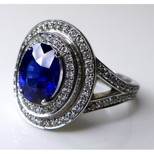 339 - An 18ct white gold, sapphire and diamond dress ring, the dark cornflower blue oval cut stone of appr...