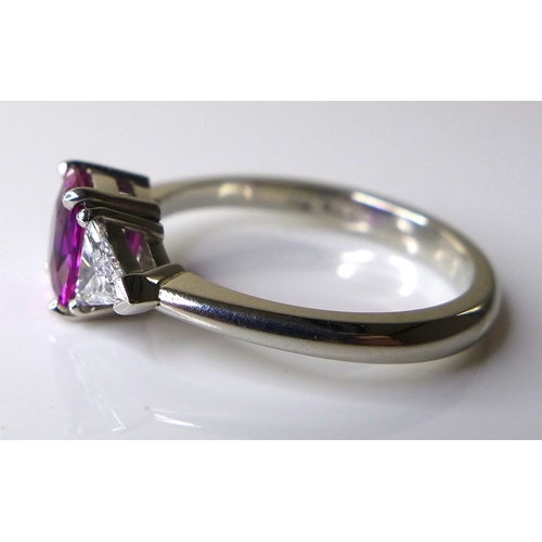 336 - A platinum, ruby and diamond three stone ring, the central cushion cut pink ruby of approximately 1c...