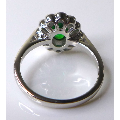 335 - An 18ct white gold, tsavorite garnet and diamond dress ring, the stunning central oval cut stone of ...