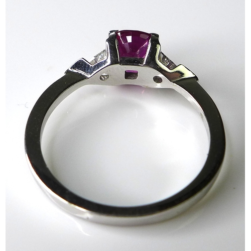 327 - An 18ct white gold, pink sapphire and diamond dress ring, the central sapphire of approximately 1.4c...