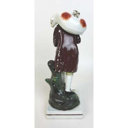 28 - An early 19th century Staffordshire pottery figure, modelled as a shepherd carrying a sheep over his...
