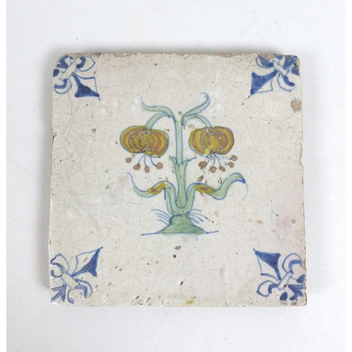 26 - A 17th century Delft polychrome tile, decorated with a central flower and with a fleur-de-lis to eac...