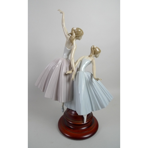 30 - A large Lladro figural group, modelled as a pair of ballerinas, with turned wooden base, 50cm high i...