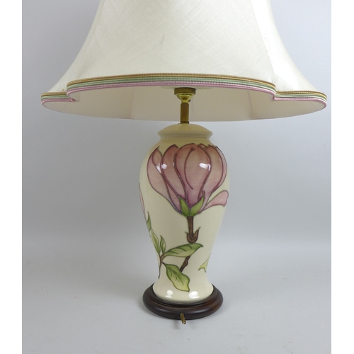 52 - A Moorcroft pink magnolia pattern table lamp with wooden stand, lamp base only 13.5 by 29cm high and...