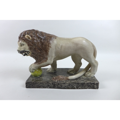 1 - A 19th century Staffordshire figure, modelled as a Medici lion, in standing pose with left paw resti...