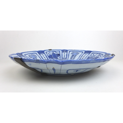 24 - Three pieces of 19th century Delft blue and white ceramics, a later 19th century charger with a rive...
