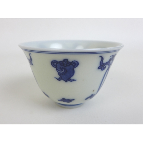 108 - A pair of Kangxi style blue and white porcelain tea bowls, each decorated with Buddhist symbols, bea...